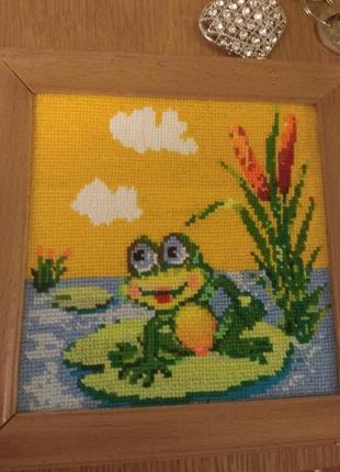 Вишита картинка жабка в дерев'яній рамці.