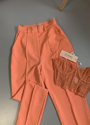 Оранжевые брюки на высокой посадке