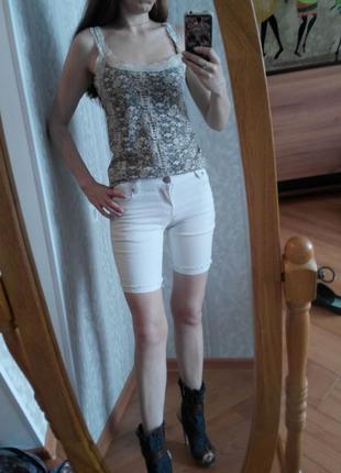 Длинные белые джинсовые шорты декорированы потертостями от pink woman