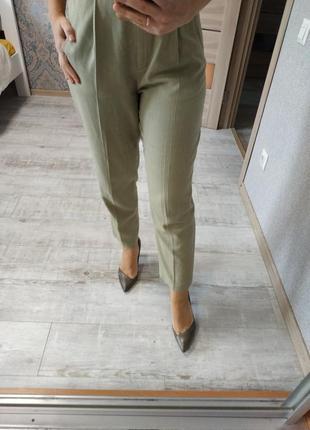Высокие актуальные брюки с защипами оливкового цвета