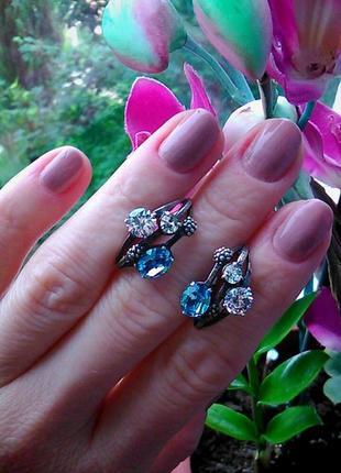 Комплиментарные серебряные серьги с голубым камнем.