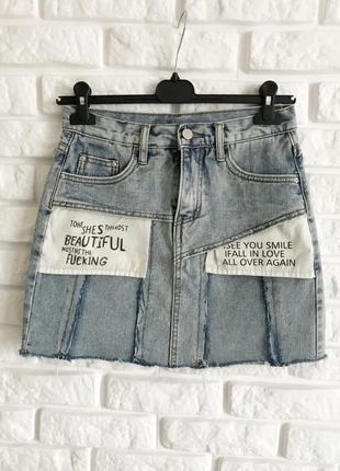 Стильна джинсова спідничка з надписами і необробленим низом