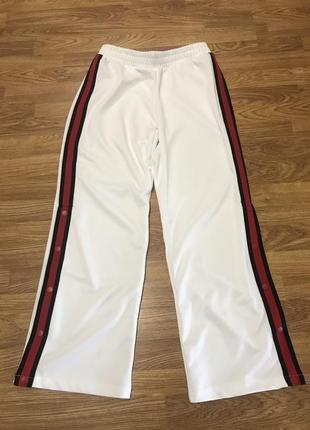 Белые, широкие, свободные брюки с красными лампасами. terranova