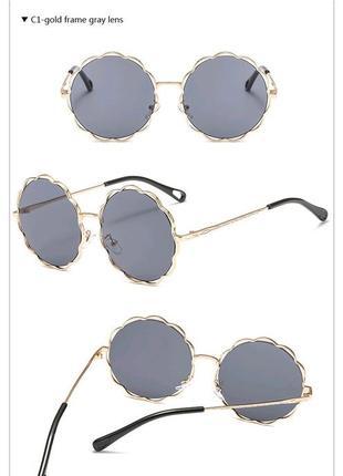 Круглые очки от солнца с волнистой золотой оправой и черной дымчатой линзой