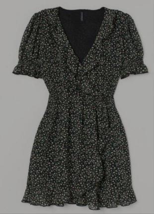 Короткое платье из воздушной ткани с глубоким треугольным вырезом с оборкой и пришитым запахом на потайной кнопке спереди.