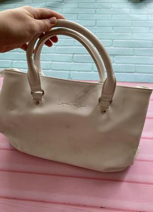 Белая сумка с короткими ручками.