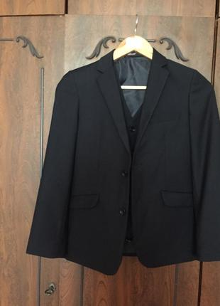 Комплект для школьника 8-9 лет: пиджак и жилетка темно-синего цвета.