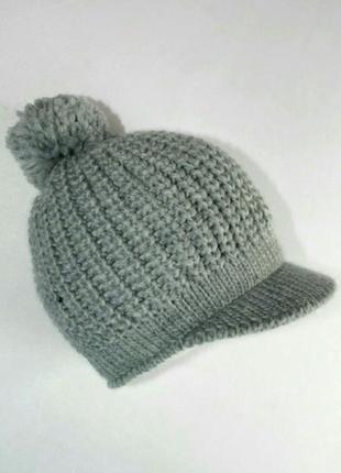 Модная вязаная шапка с козырьком и помпоном от takko fashion accessories.
