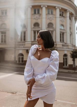 Белое силуэтное платье с объемными рукавами и ассиметричной юбочкой