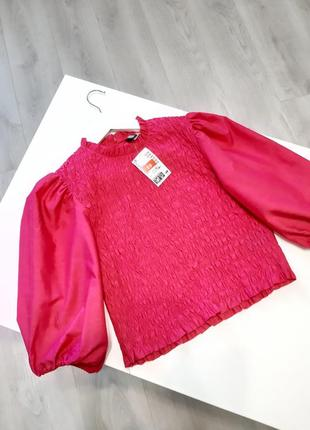 Топ-блуза з об'ємними рукавами кольору фуксія.
