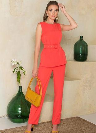 Брючный костюм морковногоцвета, состоящий из топа и брюк.