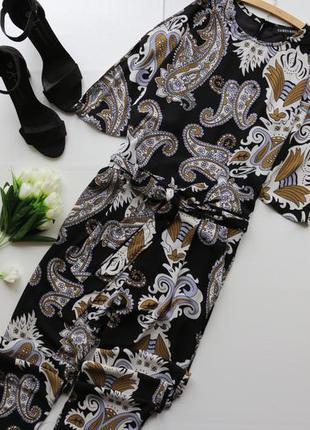 Красивый комбинезон в принт с карманами по бокам и вырезами на плечах