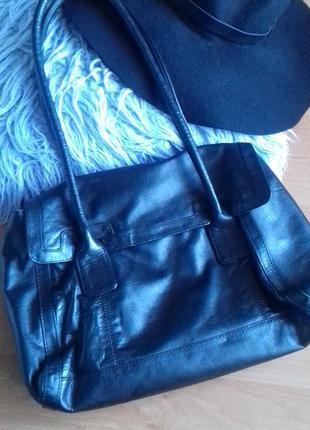 Черная сумка из натуральной кожи с ручками средней длины.