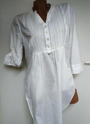 Белая удлиненная рубашка с карманами.