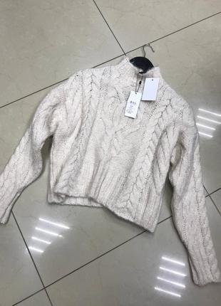 Молочный короткий свитер в косы