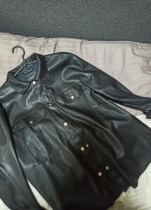 Черная легкая куртка-рубашка из искусственной кожи с застежкой на кнопки, передним карманом и длинными рукавами.