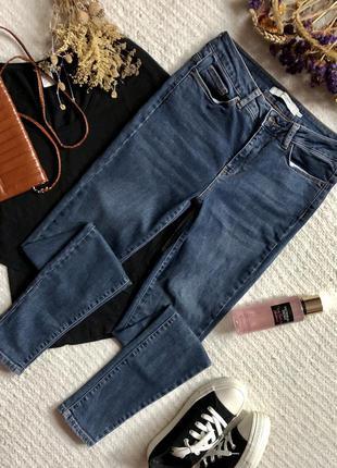 Зауженные джинсы с завышенной посадкой и потёртостями синего цвета