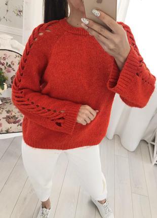 Яркий свитер с плетением на рукавах