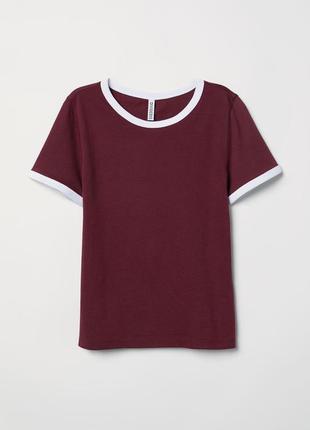 Короткая футболка из мягкого трикотажа с окантовкой контрастного цвета по горловине и низу рукавов.