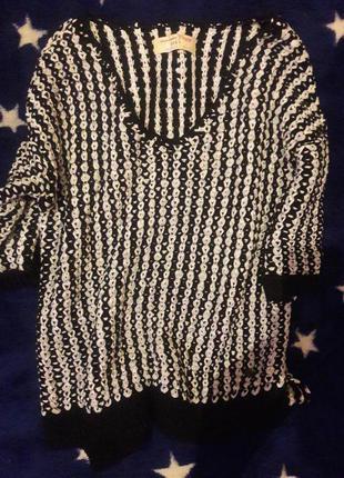 Удлинённый чёрно-белый свитер.