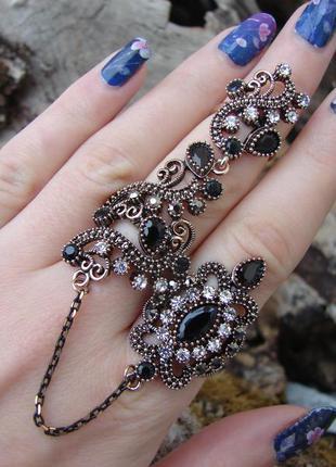 Модное крупное кольцо на два пальца с черными камнями с цепочкой. цвет бронза золото