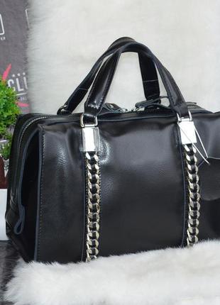 Шикарная кожаная сумка в виде бочонка с декоративными цепями.