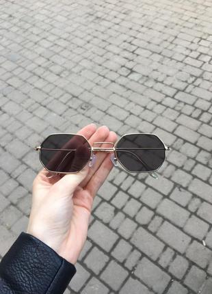 Чорні окуляри з золотою оправою