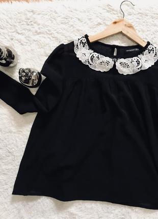 Чёрная блуза с кружевным воротником.