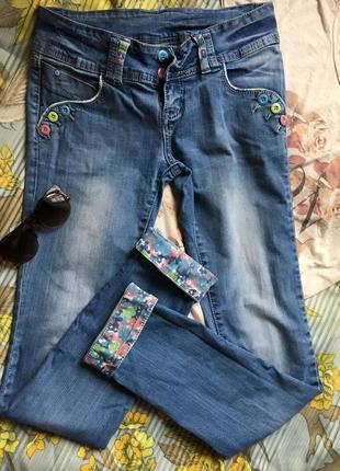 Стильные джинсы с цветочными подворотами
