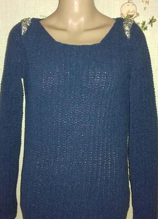 Синий свитер с украшением на плечах.