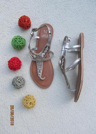 Босоножки серебристого цвета украшены бисером и стразами
