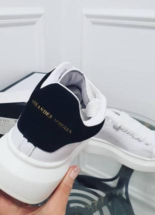 Белые кожаные кроссовки с черным задником на массивной подошве.