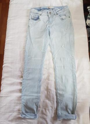 Стильные слегка рваные джинсы