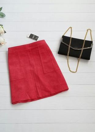 Красная вельветовая юбка с накладными карманами.