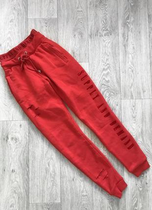 Красные спортивные штаны с рваностями supply and demand