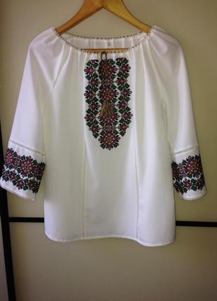 Вишивана блузка молочного коліру.