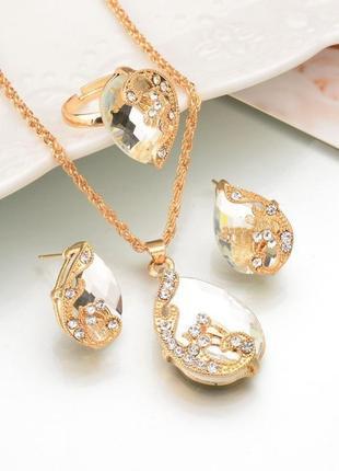 Набор: цепочка, серьги, кольцо золотистого цвета с белым кристаллом, украшено камнями