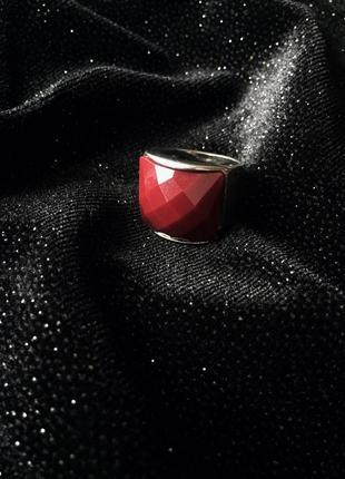 Кольцо серебристого цвета с бордовой вставкой.