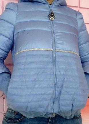 Пуховик небесно голубого цвета с капюшоном.