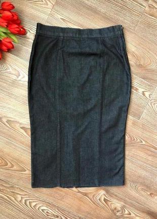 Темная джинсовая юбка ниже колена с разрезом сзади.