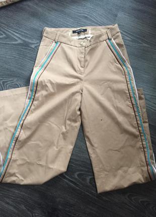 Красивые брюки с высокой посадкой и интересными лампасами очень модного цвета