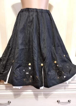 Черная юбка с перфорацией на подоле и с белой юбкой с вышивкой внутри.