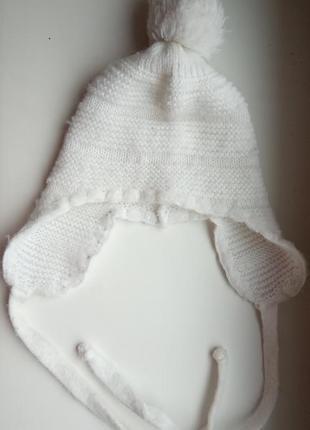 Белая вязаная шапка шапочка