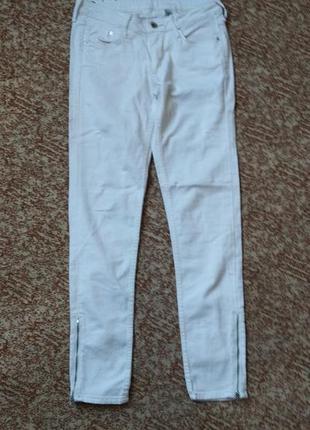 Белые джинсы скини на средней посадке с замочками замками