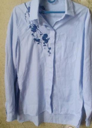 Рубашка в полоску с вышивкой сзади длиннее.