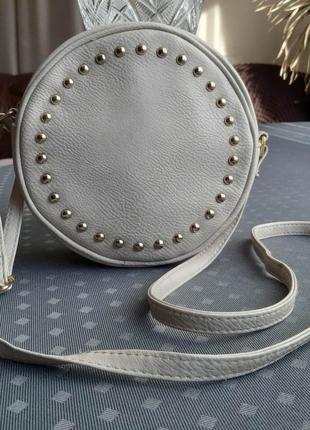 Красивая круглая бежевая сумка кроссбоди с металическими заклепками фирмы atmosphere
