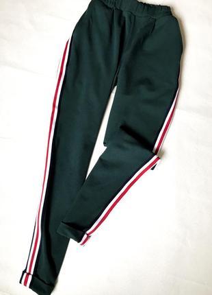 Актуальные повседневные спортивные штаны зеленого цвета с лампасами
