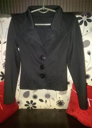 Коротенький пиджачек с красивым украшением.