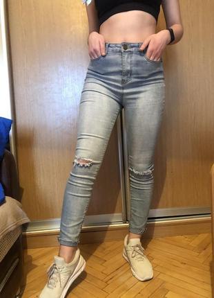 Блакитні джинси з рваними колінами