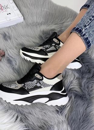 Чёрные кроссовки с белой подошвой и принтом под рептилию.
